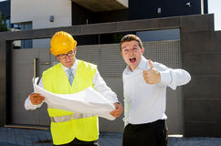 Happy customer and constructor foreman worker talking on new house building blueprints in real state business concept. Happy customer smiling giving thumb up and stock photography