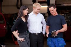Happy Customer Couple with Mechanic. A happy customer couple receiving repair report from smiling men mechanic royalty free stock photos