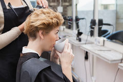 Happy customer enjoying some tea. At hairdressers Stock Image