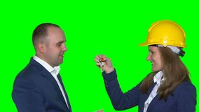 Happy customer get keys from his new house from pretty realtor woman with helmet. On head. Green even chroma key background. Static closeup shot. 4K UHD stock video