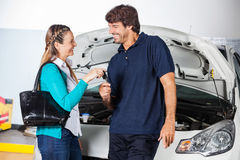 Happy Customer Giving Car Keys To Mechanic Royalty Free Stock Image