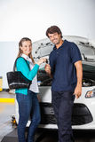 Happy Customer Giving Car Keys To Technician. Portrait of happy female customer giving car keys to technician in auto repair shop Stock Photography