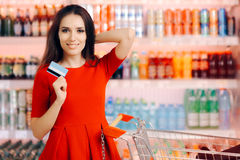Happy Customer Holding Credit Card in a Supermarket Royalty Free Stock Images