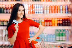Happy Customer Holding Credit Card in a Supermarket Royalty Free Stock Photos
