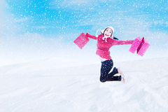 Happy customer jumping with bags in winter snow Royalty Free Stock Photo