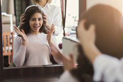 Happy customer looking in mirror after haircut stock photos