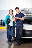 Happy Customer And Mechanic With Digital Tablet In. Portrait of happy female customer and mechanic with digital tablet standing by car in garage Stock Images