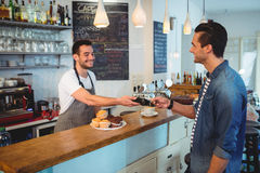 Happy customer paying through credit card at coffee shop Royalty Free Stock Photo