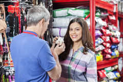 Happy Customer With Salesman Holding Guinea Pig In Store. Portrait of happy female customer with salesman holding guinea pig in pet store Royalty Free Stock Images