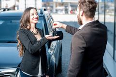Happy customer and seller near the car. Happy female customer receiving keys from a new car standing near the modern avtosalon stock photo