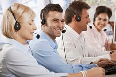 Happy customer service operator. Happy young customer service operator talking via headset, typing on keyboard, looking at camera, smiling Stock Image