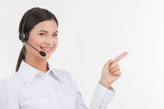 Happy customer service representative. Beautiful young female customer service representative in headset pointing away and looking at camera while isolated on Stock Images