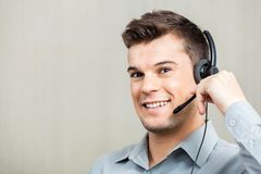Happy Customer Service Representative Wearing. Portrait of happy male customer service representative wearing headset at office Stock Photography