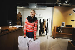 Happy customer with shopping bag in fashion showroom. She smiles Stock Images