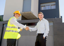 Happy customer smiling and constructor foreman worker handshake agreement in real state business. Happy customer smiling and constructor foreman worker with royalty free stock image