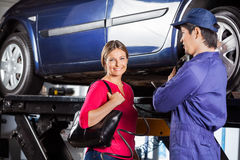 Happy Customer Standing With Technician At Garage. Portrait of happy female customer standing with technician at garage Royalty Free Stock Image