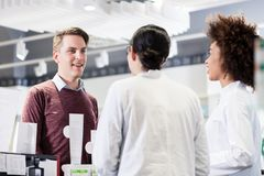 Happy customer talking with two helpful pharmacists in a contemp Royalty Free Stock Photography