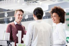 Happy customer talking with two helpful pharmacists in a contemporary drugstore royalty free stock photos