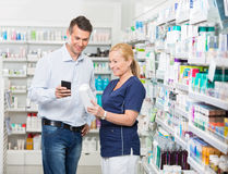 Happy Customer Using Mobile Phone While Pharmacist. Happy male customer using mobile phone while pharmacist holding products in pharmacy royalty free stock image