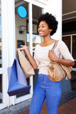 Happy customer walking outside store with shopping Stock Photos