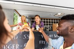 Happy customers buying burger at food truck Royalty Free Stock Images
