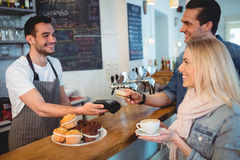 Happy customers paying through card at cafe. Happy customers paying through card while looking at male barista in cafe Royalty Free Stock Photos