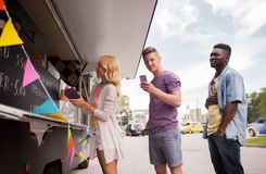 Happy customers queue at food truck. Street sale and people concept - happy customers queue at food truck Royalty Free Stock Photos