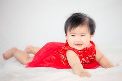 Happy cute asian baby girl in chinese tradition dress smiling. And crawling in the bed Royalty Free Stock Image