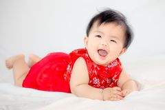 Happy cute asian baby girl in chinese tradition dress smiling. And crawling in the bed Royalty Free Stock Images