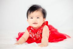 Happy cute asian baby girl in chinese tradition dress smiling. And crawling in the bed Stock Image