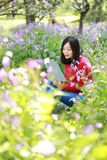Happy cute Asian Chinese nature beautiful woman girl in a spring park enjoy free time read book stock image