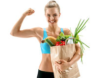 Happy cute athletic woman showing biceps with grocery bag full of healthy fruits and vegetables Royalty Free Stock Photos