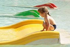 Happy cute baby boy plays on yellow waterslide. Happy cute baby boy with blond hair plays on yellow waterslide in outdoor pool on sunny summer day on water Royalty Free Stock Photo