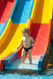 Happy cute baby boy rides from waterslide Stock Photos