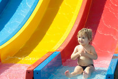 Happy cute baby boy rides from waterslide Royalty Free Stock Photography