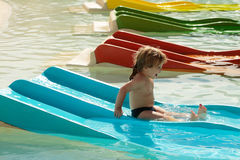 Happy cute baby boy slides from blue waterslide Royalty Free Stock Photos
