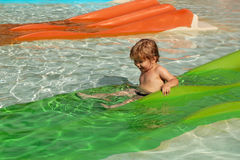 Happy cute baby boy slides from green waterslide Stock Image