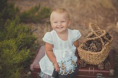 Happy cute baby girl with blond hairs and blue eyes wearing retro old style modish white dress posing smiling in central park betw. Een green tree bush sitting Royalty Free Stock Photos