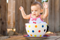 Happy and cute baby girl in giant teacup Royalty Free Stock Photos