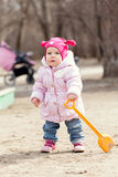 Happy cute baby girl walks in spring park Stock Photos
