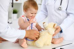 Happy cute baby at health exam at doctor`s office. Toddler girl is sitting and keeping stethoscope and teddy bear.  Royalty Free Stock Photo