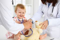 Happy cute baby at health exam at doctor`s office. Toddler girl is sitting and keeping stethoscope and teddy bear.  Royalty Free Stock Photography