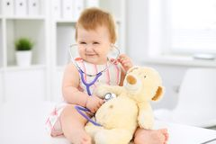 Happy cute baby at health exam at doctor`s office. Toddler girl is sitting and keeping stethoscope and teddy bear.  Stock Photo