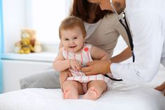 Happy cute baby with her mother at health exam at doctor`s office. Happy cute baby with her mother at health exam at doctor`s office Stock Photos