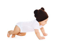 Happy cute baby in knitted brown hat crawls on white background. Profile view Stock Image