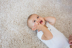 Happy cute baby lying on carpet Royalty Free Stock Photos
