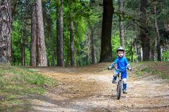 Happy cute blond kid boy having fun his first bike on sunny summ Stock Images
