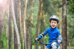 Happy cute blond kid boy having fun his first bike on sunny summ Stock Photos