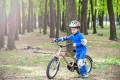 Happy cute blond kid boy having fun his first bike on sunny summer day, outdoors.  child making sports. Active leisure for childre Stock Photography