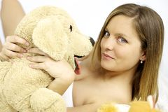 Happy cute blond woman with stuffed toy dog Royalty Free Stock Images